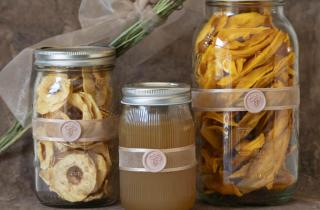Glass jars with dried fruit and honey inside, decorated with a beige ribbon and a sealing medallion with a champagne-colored bee figure.