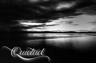 Landscape photography with mountains and sea in black and white and the word quietude