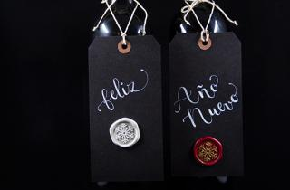 Wine bottles with tags hanging with text Happy New Year and sealing medallions on tag