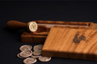 Wooden case with engraved rooster in the center, sealing wax seal with logo of rooster and medallions in golden rose color
