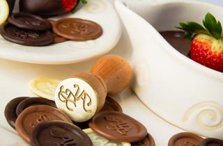 Metallic seal to seal chocolates, surrounded by chocolates stamped with the seal of ALB and some strawberries covered with chocolate on white ceramic