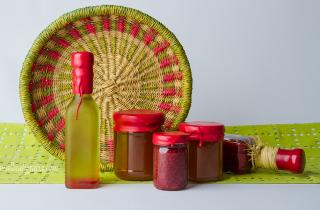 Bottles of oil and canned preserves wax dipping in red color, decoration with a basket of wicker and a green cloth