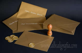 Gold envelopes, labeled in cream color calligraphy and sealed with gold sealing wax stickers